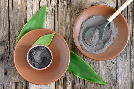 신선한 녹색 잎으로 장식 세라믹 그릇에 화장품 점토. 스파 몸과 얼굴 치료