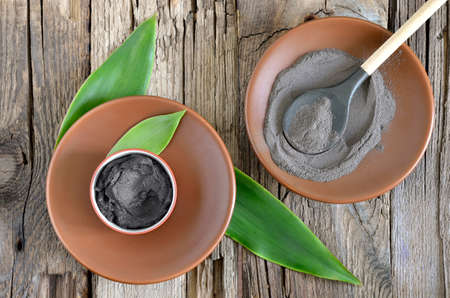 Cosmetic clay in a ceramic bowl decorated with fresh green leaves. Spa body and face treatment Standard-Bild