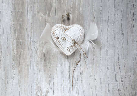 long lasting: Grunge rustic Valentine heart with feather wings. Long lasting love simbol