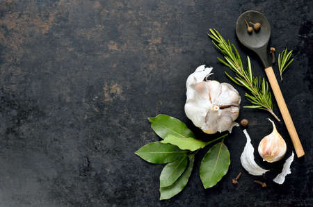 european food: Dark culinary background with a wooden spoon along with garlic, rosemary, bay leaves,  pepper and some cloves pictured on it