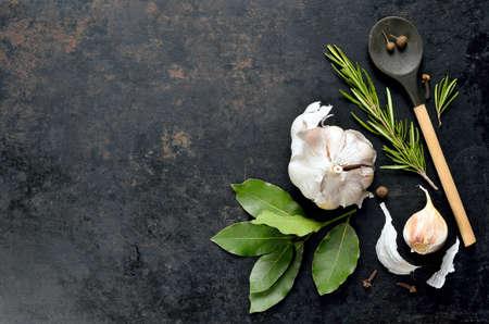 pepe nero: Sfondo culinario scuro con un cucchiaio di legno con aglio, rosmarino, alloro, pepe e qualche chiodo di garofano raffigurato su di esso
