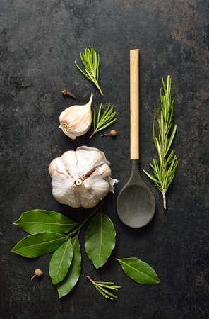 木のスプーン、ニンニク、月桂樹の葉、ローズマリーとグランジ キッチンの背景