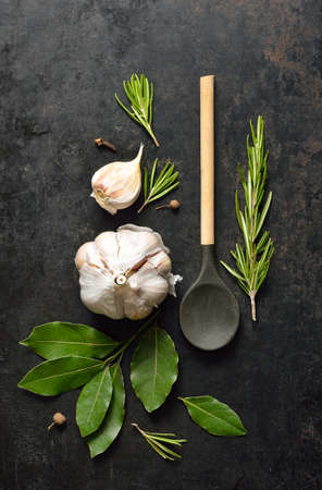 Fundo da cozinha Grunge com colher de madeira, alho, folhas de louro e alecrim Imagens