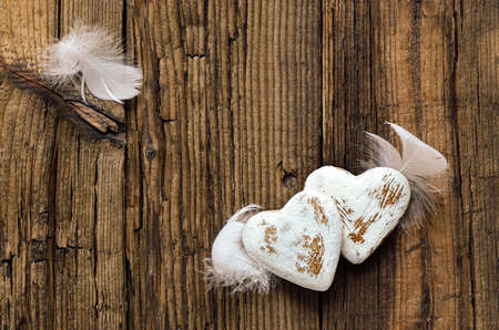 long lasting: Rustic grunge hearts with feather wings on a weathered wooden background, mutual long lasting love symbol Stock Photo