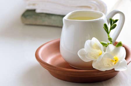新鮮な花で飾られた白い水差しのマッサージ オイル