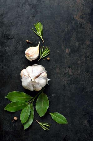 ニンニク、ローズマリー、月桂樹の葉、唐辛子、それで描かれるいくつかのクローブと暗いの料理の背景