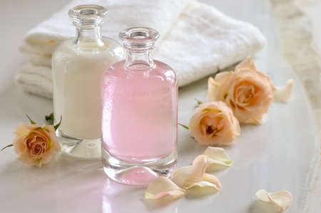 Cosmetic liquids, maybe milk, shampoo or toner, in glass bottles decorated with roses.