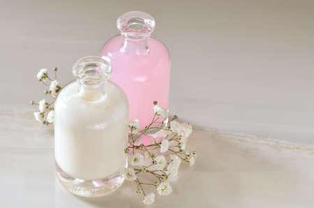 Líquidos cosméticos, talvez leite, xampu ou toner, em garrafas de vidro decoradas com flores brancas. Imagens