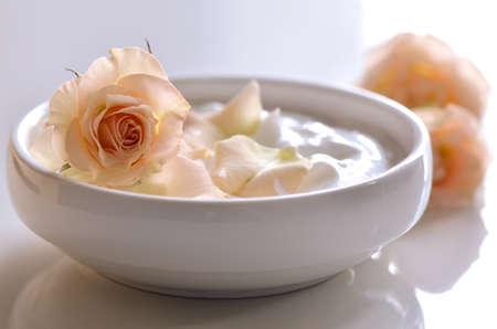 自然の顔や体クリーム ホワイト ポットにバラの花びら。自家製天然化粧品。