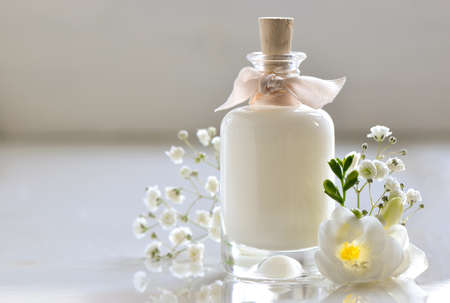Body or face skin care lotion decorated with flowers as present Foto de archivo
