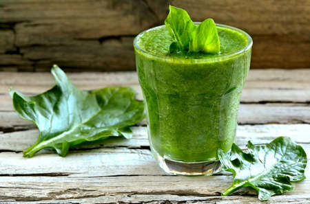 green herbs: Green spinach smoothie in a glass with fresh leaves Stock Photo