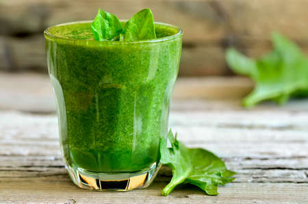 Green spinach smoothie in a glass with fresh leaves Standard-Bild