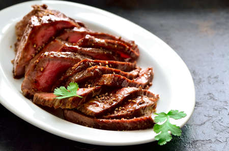 Juicy flank steak in an oval white plate decorated with cilantro leaves Foto de archivo