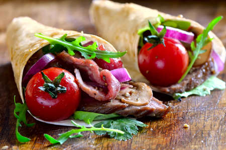 spanish onion: Spicy wpapped fajitas with grilled beef and various greens such as lettuce, cilantro arugula and spanish onion