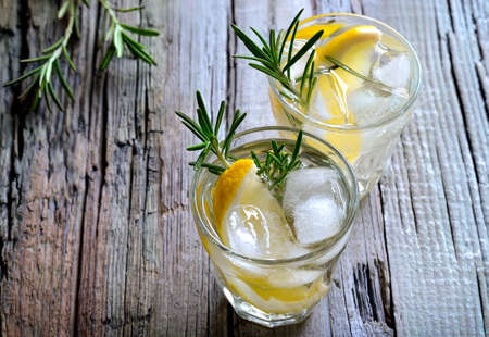 Lemon and rosemary soda with ice cubes in glasses or maybe refreshing summer alcoholic cocktail