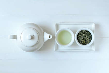 Green tea in tea pot and white cups, top view