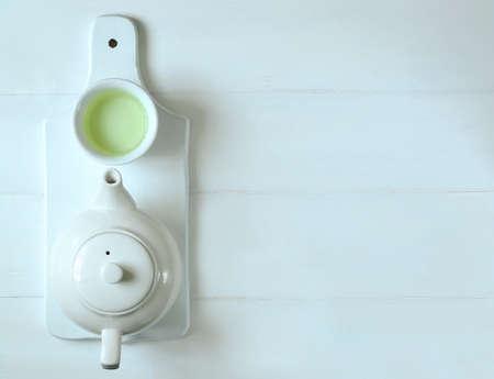 O chá verde no potenciômetro do chá e copos brancos, vista de cima