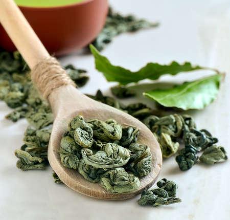 Colher de madeira com folhas de chá verde secas e um ramo de folhas de chá verde nos bastidores