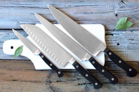 Conjunto de cuchillos de cocina en una tabla, vista superior Foto de archivo