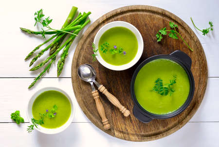 Green spring pureed asparagus soup served in plates decorated with various garden herbs