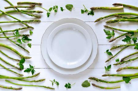 きれいな食べるか、または健康食品のコンセプトの背景、グリーン アスパラガスと白ビンテージ プレート、トップ ビューの周りの様々 なハーブ