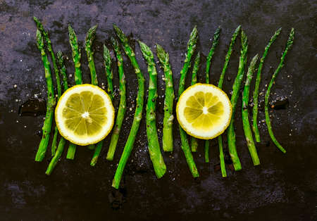 Roasted asparagus seasoned with salt, pepper, balsamic vinegar and decorated with lemon
