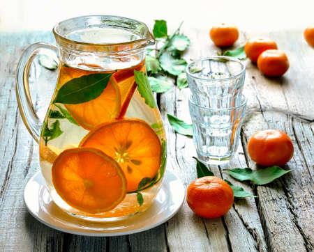 自家製柑橘類は、晴れた日に素朴な背景に水差しの水を注入