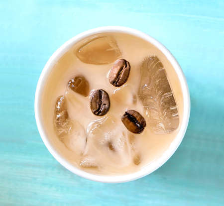 Iced coffee with milk or cream in paper one-off cup, top view Standard-Bild