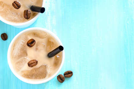 above: Iced coffee with milk or cream in paper one-off cups with a straws, top view