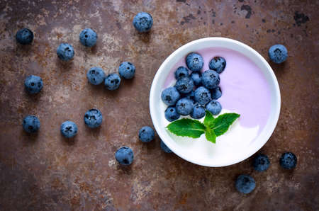 Light greek yogurt or cream dessert with fresh blueberries served in white bowl, top view, stylized photo
