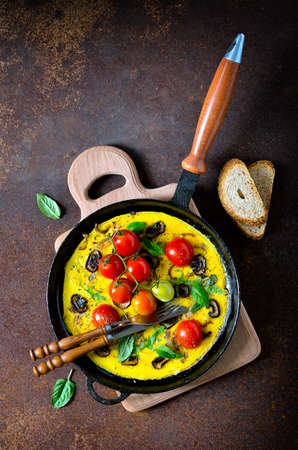 huevos revueltos: Frittata or omelet with mushrooms and tomatoes in a pan, traditional mediterranian course, top view, vertical