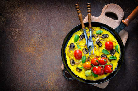 mediterranian: Frittata or omelet with mushrooms and tomatoes in a pan, mediterranian course, top view
