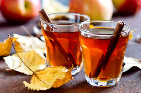 warm drink: Apple cider with cinnamon sticks in glasses decorated with autumn yellow leaves Stock Photo