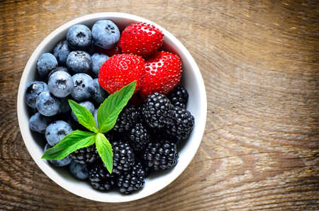 Various berries in a white bowl, top view