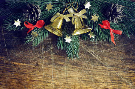firry: Christmas vintage background with firry branches decorated with golden bells, stylized image Stock Photo