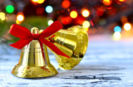 jingle: Golden bells with red bow on a weathered wooden surface