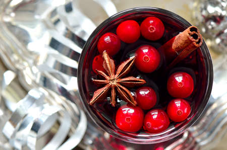 Cristmas traditional warm alcohol drink or cocktail with spices and cranberries surrounded with sparkling decorations
