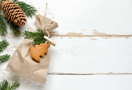 fir twig: Christmas background with a simple handmade present decorated with gingerbread and fir twig