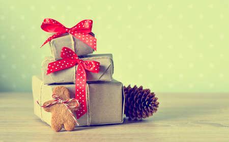 Presentes de Natal simplesmente embrulhados decorados com arcos de bolinhas vermelhos, foto estilizada vintage Imagens