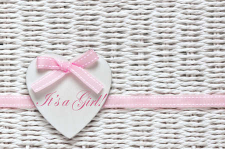 arrival: Baby shower card or invitation for baby girl with white wooden decorative heart with text on it Stock Photo