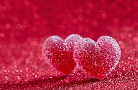 corações Marmalade coberto com açúcar em um fundo vermelho brilhante