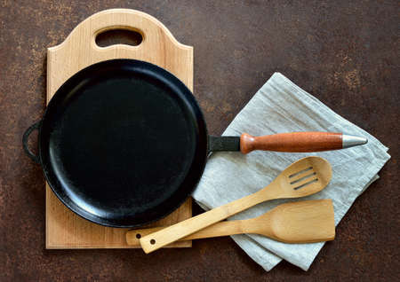 cast iron pan: Cast iron pan and other kitchen  utensils on a dark brown aged background, top view