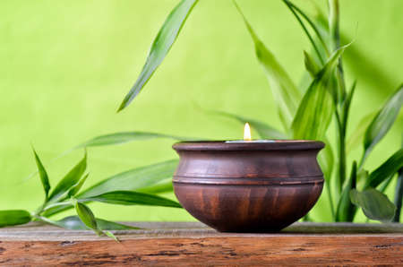 stone bowl: Aroma candle in authentic ceramic bowl decorated with green bamboo leaves, spa concept