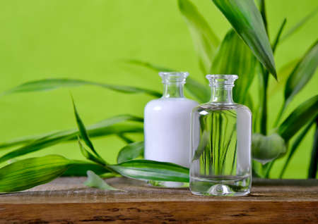 Bottles on a wooden surface decorated with fresh green leaves, organic cosmetics concept