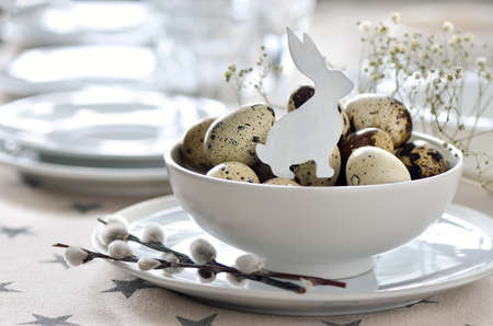 Easter table setting with white bunny decoration in a quail eggs hip