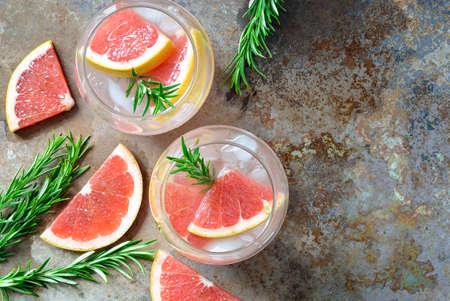 グレープ フルーツとローズマリーのお酒、アルコールやノンアルコール カクテルまたは注入された水に氷