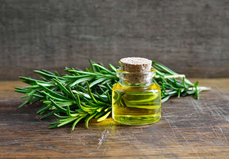 energy healing: Rosemary essential oil in a glass bottle