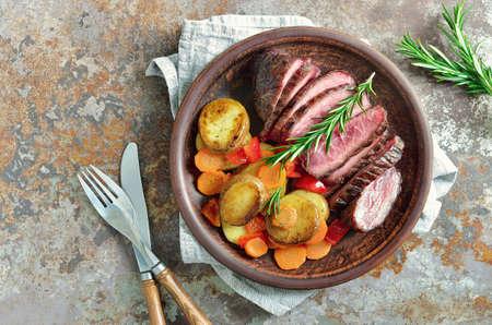 grilled potato: Roasted carrots, potato and cut meat, plain rustic dish Stock Photo