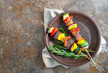 cebolla roja: Various vegetables and meat kebabs on a dark plate, view from above