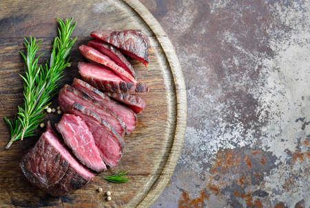 Beefstake cozido cortado em uma placa, vista superior Imagens
